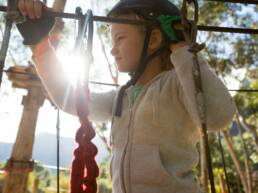 Little girl wearing helmet standing near zip line in the forest
